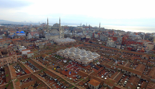 """Aerial photo taken with a drone shows the roof of Istanbul's centuries-old Grand Bazaar, foreground, Monday, Feb. 1, 2016. In a news conference Monday, the municipality of the city's Fatih district announced its plans for the renovation of the iconic maze of shops, restaurants and tea houses. The complex, which houses nearly 4,500 stores, starred in the 2012 James Bond movie, """"Skyfall.""""  Historical Nur-u Osmaniye Mosque is in the background. (Ali Aksoyer/DHA via AP)"""